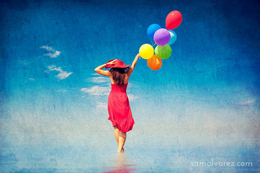 Brunette-girl-with-colour-balloons-at-coast